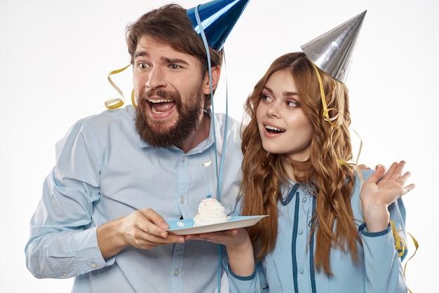 Aniversário de homem e mulher com um bolinho e uma vela em um chapéu de festa