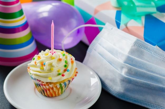 Aniversário de quarentena isolado. bolo de aniversário, máscara facial, presentes e acessórios de férias.