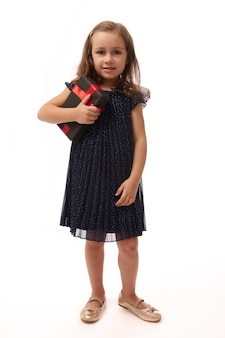 Aniversário e conceito de black friday. retrato de corpo inteiro em fundo branco com espaço de cópia de uma adorável menina criança de 4 anos vestida em traje de noite e sapatos dourados, segurando uma caixa de presente.