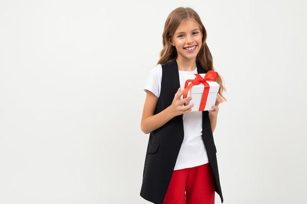 Aniversário . garota sorridente atraente com um presente com uma fita vermelha nas mãos em um branco com copyspace