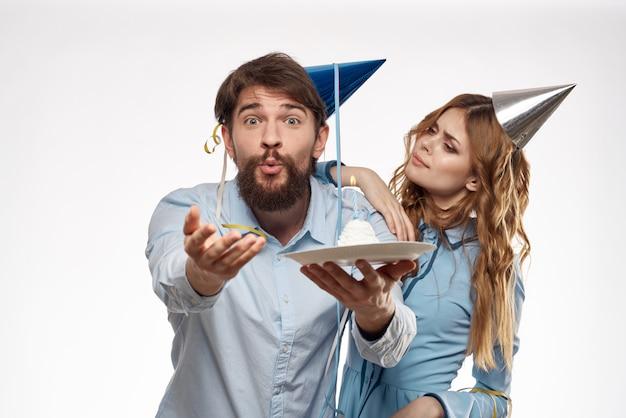 Aniversário homem e mulher com um bolinho e uma vela com um chapéu de festa