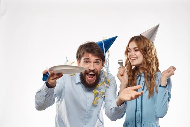 Aniversário homem e mulher com um bolinho e uma vela em um chapéu de festa, parede branca