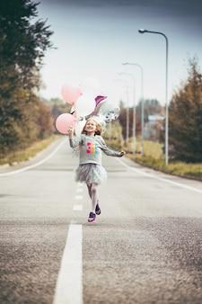 Aniversário - menina feliz com balões corre ao longo da faixa divisória da estrada