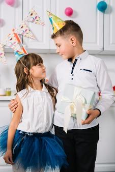 Aniversário, menino, segurando, caixa presente, em, mão, ficar, com, dela, irmã, olhando um ao outro