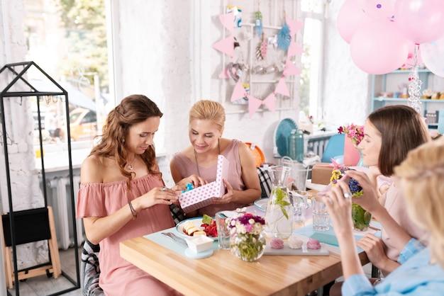 Aniversário no café. mulher grávida de cabelos escuros comemorando seu aniversário em um café com suas melhores amigas