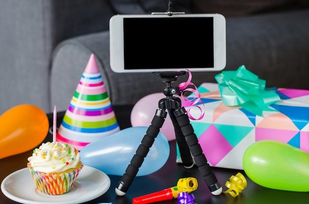 Aniversário online. smartphone, bolo de aniversário, presentes e acessórios de férias.