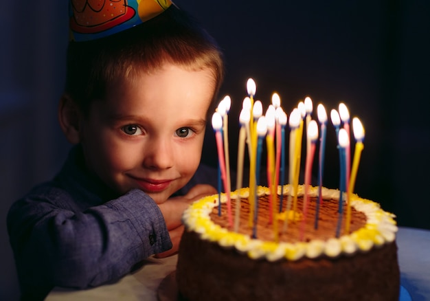 Aniversário. um garotinho apaga velas no fogão.