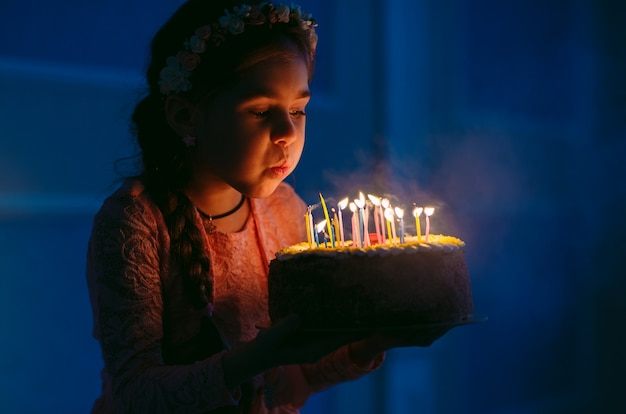 Aniversário. uma garotinha doce apaga velas no fogão.
