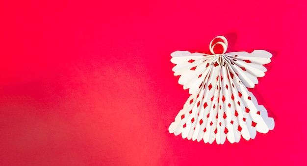 Anjo branco feito de papel sobre um fundo vermelho. copie o espaço.