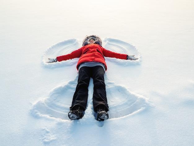 Anjo da neve feito por uma mulher feliz na neve. vista aérea plana superior.
