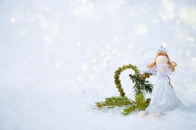 Anjo de boneca de fundo de natal, coração feito de abeto na neve com bokeh copyspace