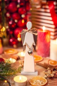 Anjo de madeira, velas acesas, decoração de natal, bolas de pinheiro na mesa