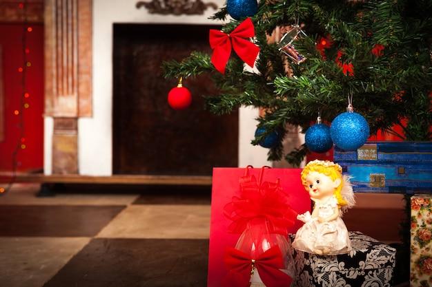 Anjo de natal com lareira em segundo plano.