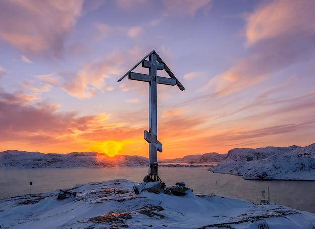 Anjo do sol sobre o monte e cruz ortodoxa no topo da montanha coberta de neve ao nascer do sol em teriberka, rússia