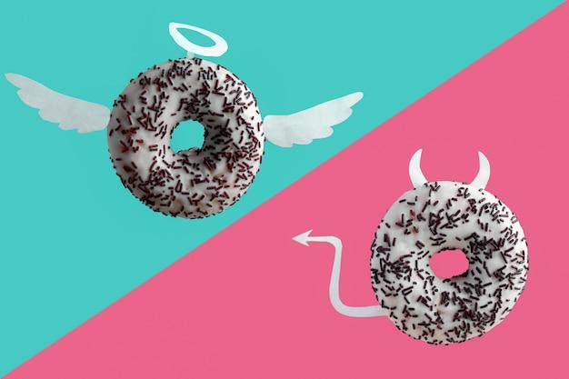 Anjo e demônio donuts em um fundo azul e rosa