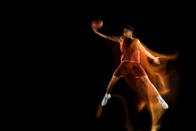 Anjo. jovem jogador de basquete muscular árabe em ação, movimento isolado em preto em uma luz mista