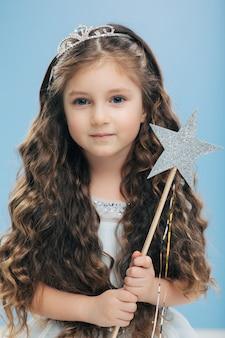 Anjo pequeno garoto tem cabelos longos e nítidos, olhos azuis, segura varinha mágica em forma de estrela