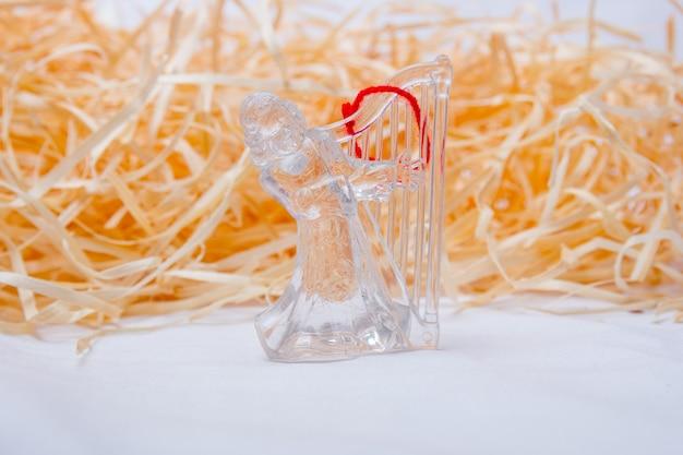 Anjo transparente para decoração de natal sobre fundo de palha no rio de janeiro.