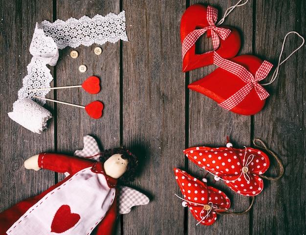 Anjo um brinquedo macio com coração, fita de renda, botões e três corações vermelhos em fundo de madeira velho. conceito de dia dos namorados. vista do topo.