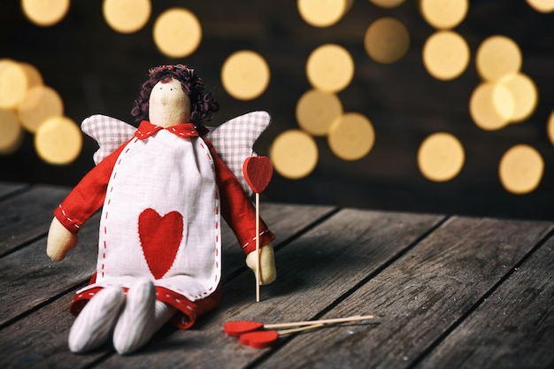 Anjo um brinquedo macio com o coração sentado no fundo de madeira velho. conceito dos namorados