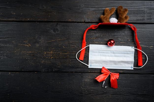 Ano de 2022 com conjunto de máscara cirúrgica e cervos, em fundo de mesa de madeira preta, vista de cima plana lay, com espaço de cópia para o texto