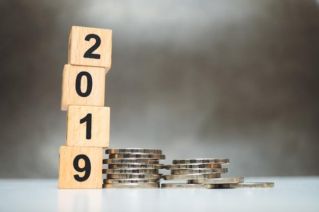 Ano de bloco de madeira 2019 com moedas de pilha usando como negócios e conceito financeiro