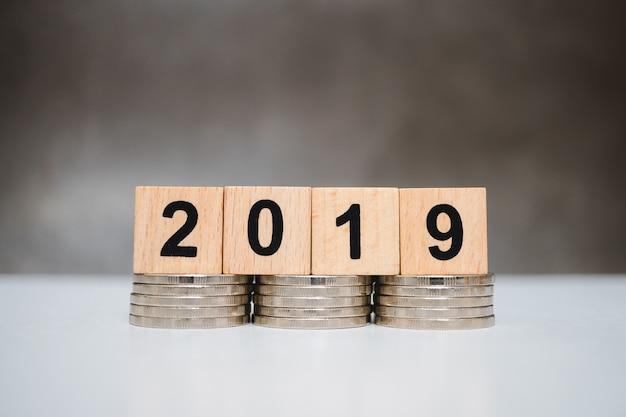 Ano de bloco de madeira 2019 em moedas de pilha usando como negócios e conceito financeiro