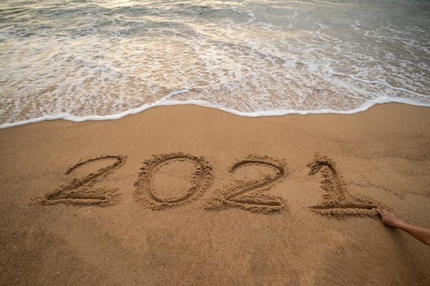 Ano de caligrafia de 2021 na areia e onda de espuma na praia.