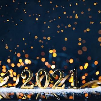 Ano de natal de números dourados com bokeh de brilho dourado em fundo azul escuro.