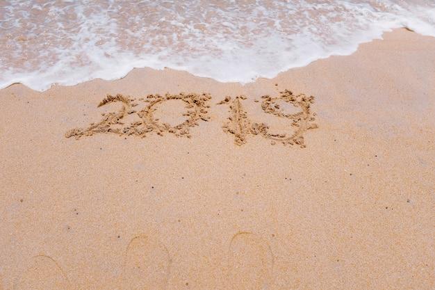 Ano novo 2019 está chegando conceito e 2018 está sendo apagado por onda no fundo da praia de areia