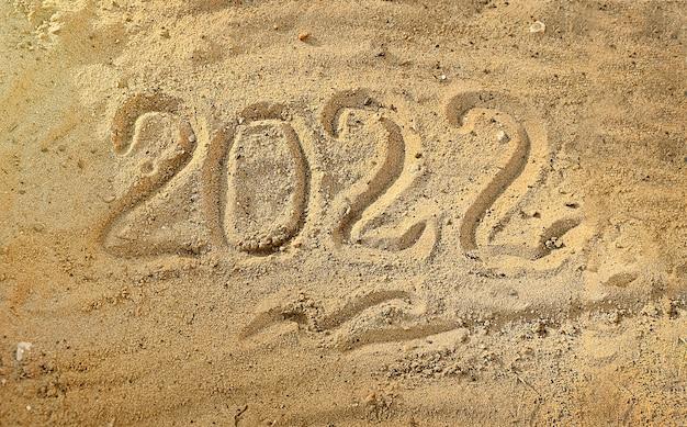 Ano novo 2022 escrito à mão na areia molhada em uma praia à beira-mar contagem regressiva na véspera do feriado