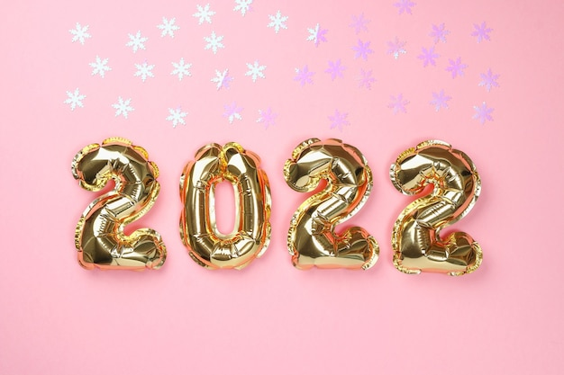 Ano novo 2022. os balões da folha números 2022 em fundo rosa.