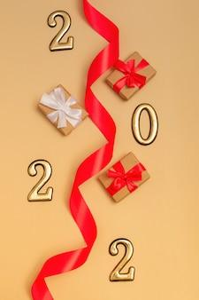 Ano novo 2022. vista superior da maquete de ano novo em fundo bege: fita vermelha, caixa de presente, números dourados e brilhos multicoloridos. layout de cartões postais, convites.