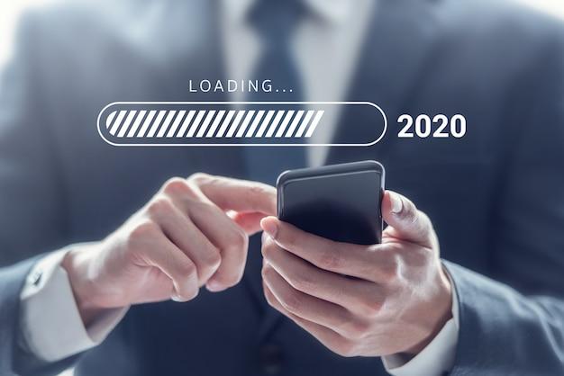 Ano novo, carregando 2020, empresário usando smartphone móvel.
