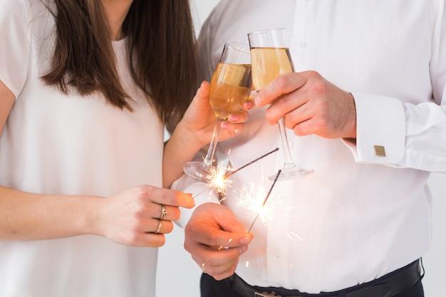 Ano novo casal apaixonado segurando estrelinhas e taças de champanhe close-up