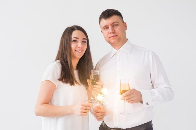 Ano novo, casal apaixonado segurando velas e taças de champanhe