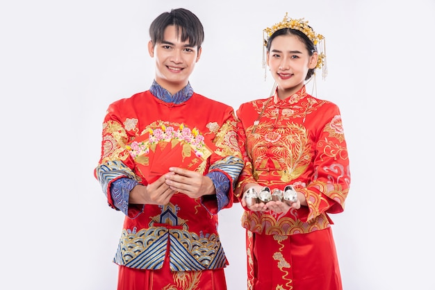 Ano novo chinês, homens e mulheres usam o sorriso cheongsam para receber - dê dinheiro e dinheiro para um parente