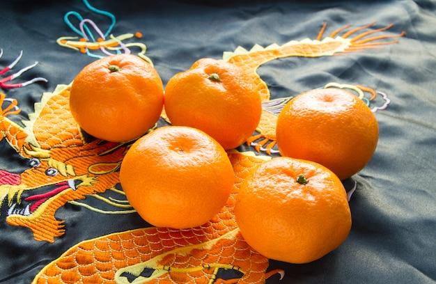 Ano novo chinês, mandarinas em tecido de seda com dragão bordado
