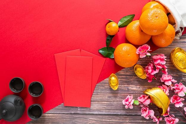Ano novo chinês oferecendo envelope vermelho bule de chá chinês e laranja