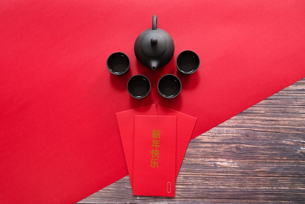 Ano novo chinês, oferecendo envelope vermelho e bule de chá chinês