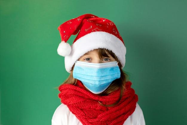 Ano novo com coronavírus. retrato do close-up de uma linda garota com um chapéu de papai noel e máscara médica protetora em uma parede verde.