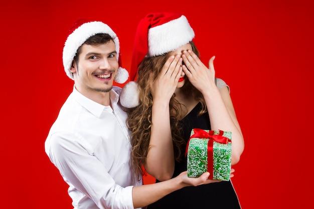 Ano novo conceito de festa de natal diversão feliz sorrindo amigos casal vestindo traje de carnaval de conto de fadas chapéu de papai noel verde surpresa presente comemorando férias de inverno isolado