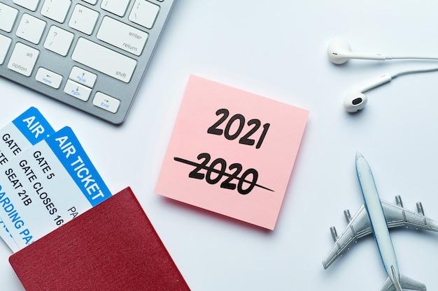 Ano novo conceito de viagens 2021 com uma inscrição em um adesivo com bilhetes nas proximidades e avião.
