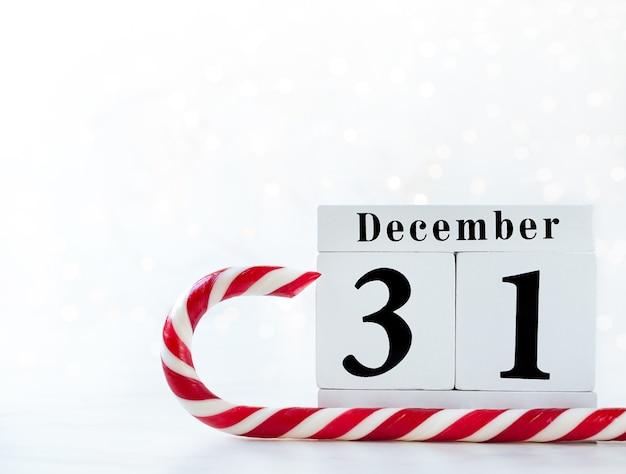 Ano novo data no calendário. calendário de madeira show de 31 de dezembro com pirulito vermelho e branco