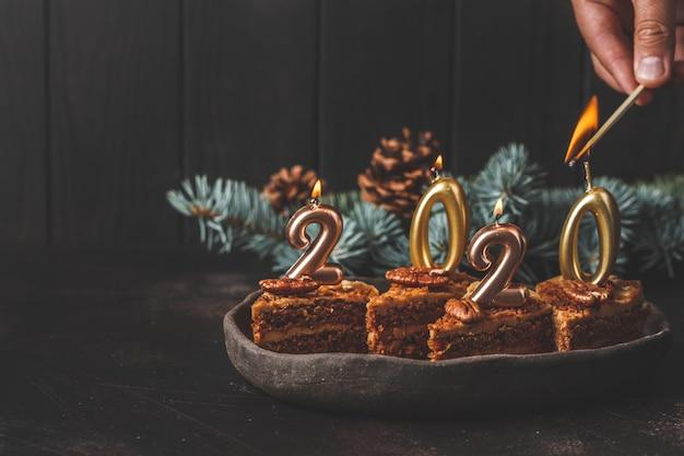 Ano novo de 2020. bolo festivo com velas na mesa escura, copie o espaço.