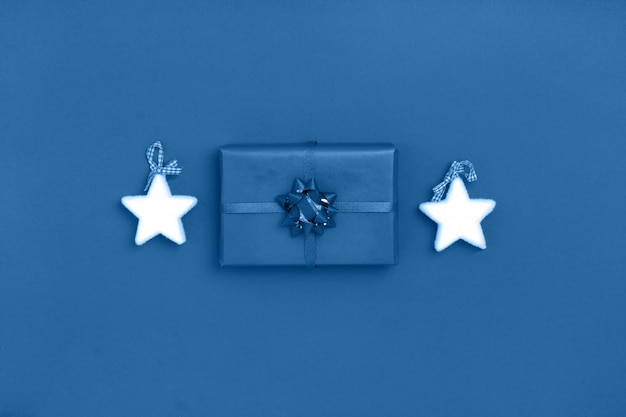 Ano novo e composição de natal de estrelas brancas, caixa de presente em fundo azul. cor na moda do ano 2020. vista superior, configuração plana, cópia espaço