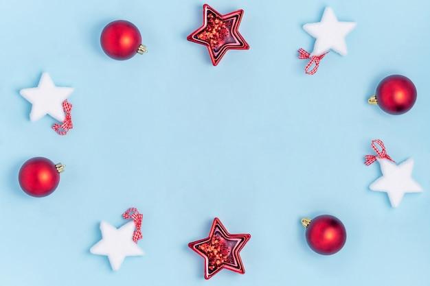 Ano novo e composição de natal. estrelas de brinquedos de vermelho e branco natal, bolas de natal em papel azul pastel. vista superior, plana leigos, copyspace