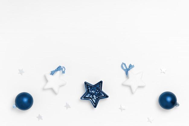 Ano novo e composição de natal. quadro de bolas azuis, estrelas brancas em papel branco. vista superior, plana leigos, copyspace. cor na moda do ano.