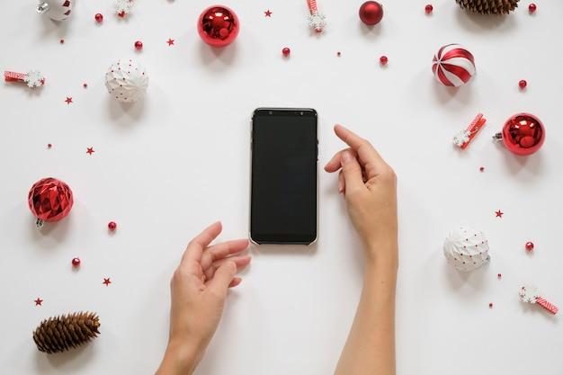 Ano novo e compras de natal. smartphone em uma mesa branca com decorações vermelhas