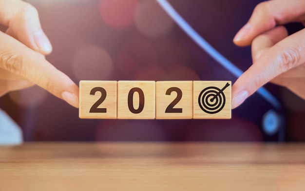 Ano novo e metas para o conceito de sucesso, mãos segurando blocos de madeira